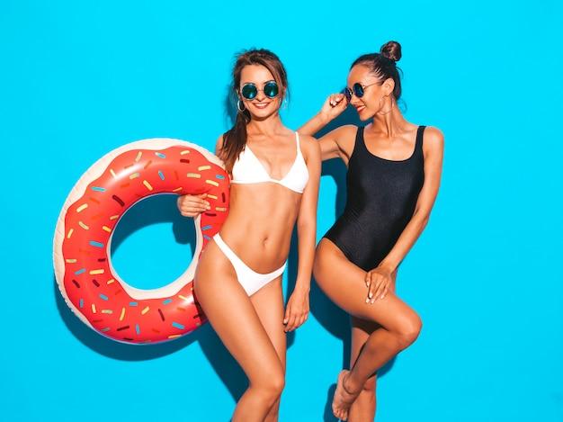 Dwie piękne seksowne uśmiechnięte kobiety w białych i czarnych strojach kąpielowych w lecie. dziewczyny w okularach przeciwsłonecznych. pozytywne modele zabawy z dmuchanym materacem lilo na białym tle na niebieskiej ścianie