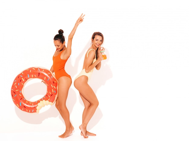 Dwie piękne seksowne uśmiechnięte kobiety w kolorowe kolorowe stroje kąpielowe kostiumy kąpielowe. dziewczyny na białym tle. zabawne modele pijące świeży koktajl smoozy z dmuchanym materacem lilo z pączków