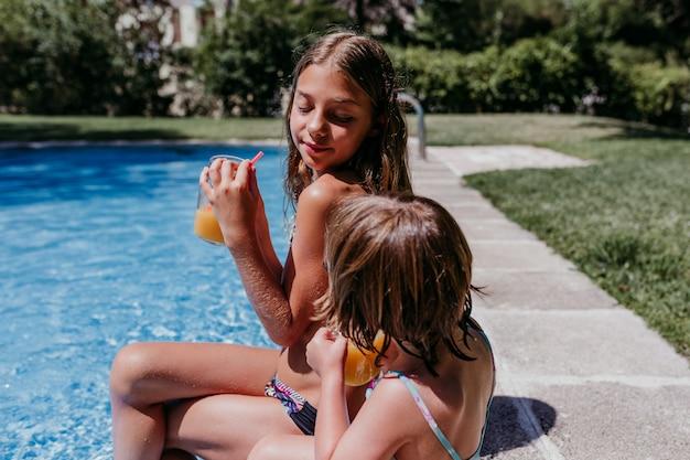 Dwie piękne siostry na basenie, picie zdrowego soku pomarańczowego i zabawy na świeżym powietrzu. koncepcja czasu letniego i stylu życia
