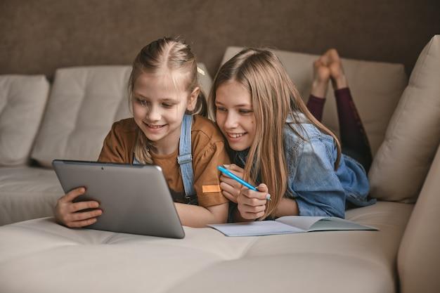 Dwie piękne siostry odrabiają lekcje podczas kwarantanny. dzieci używają gadżetów do nauki.
