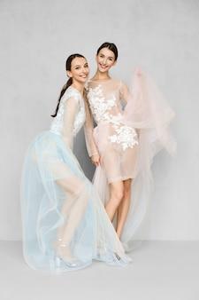 Dwie piękne siostry podrzucają rąbek jasnych przezroczystych sukienek z koronkowymi detalami