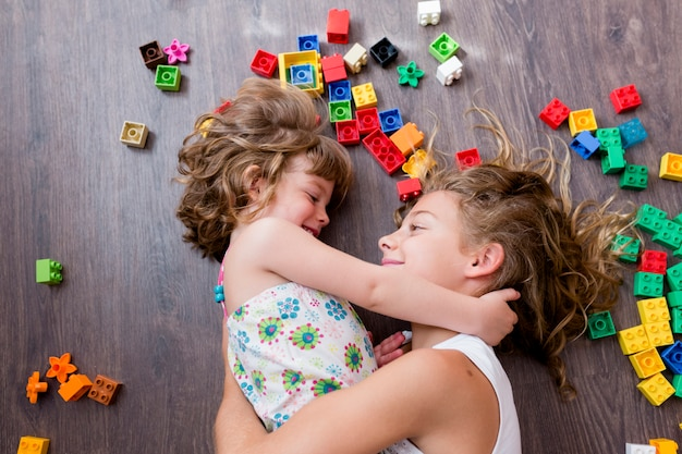 Dwie piękne siostry rodzeństwo bawi się blokami budowy zabawki. dzieci bawiące się w łaskotki.