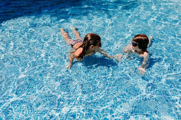 Dwie piękne siostrzane dziewczynki pływające w basenie z nowoczesnymi okularami przeciwsłonecznymi. zabawa na świeżym powietrzu. koncepcja czasu letniego i stylu życia