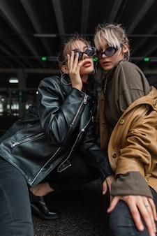 Dwie piękne stylowe miejskie dziewczyny z modnymi okularami przeciwsłonecznymi i vintage skórzanymi kurtkami ze swetrem pozują w mieście. przyszły styl młodzieżowy