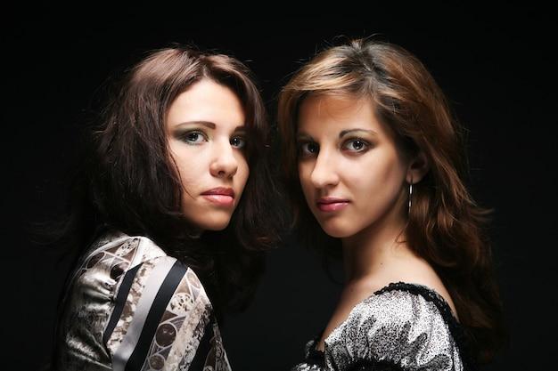 Dwie piękne szczupłe seksowne młode dziewczyny z jasnym makijażem