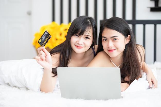 Dwie piękne tajki miała na sobie piżamę i leżała w łóżku. trzyma w niej kartę kredytową i laptopa. koncepcje homoseksualne i lesbijskie