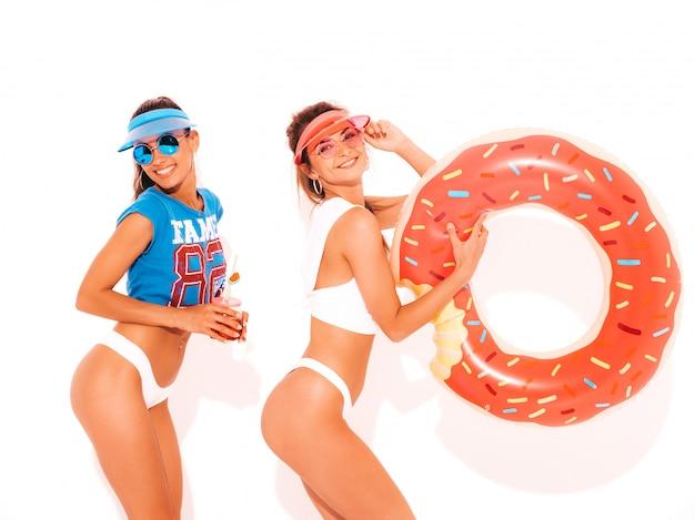 Dwie piękne uśmiechnięte seksowne kobiety w białych majtkach i temacie. dziewczęta w okularach przeciwsłonecznych, przezroczysta czapka z daszkiem. modele piją świeży, smoozowy napój koktajlowy z dmuchanym materacem lilo z pączków