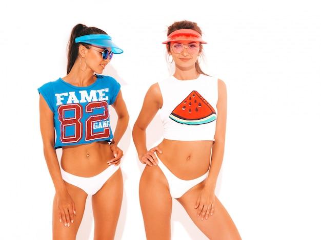 Dwie piękne uśmiechnięte seksowne kobiety w białych majtkach i temacie. dziewczyny w okularach przeciwsłonecznych i przezroczystej czapce. modne modele zabawy. pojedynczo na białym