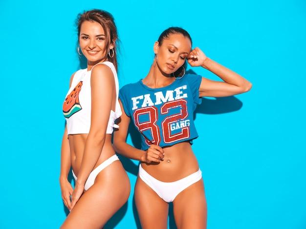 Dwie piękne uśmiechnięte seksowne kobiety w białych majtkach i temacie. modne modele dziewczyn świetnie się bawią. odosobniony