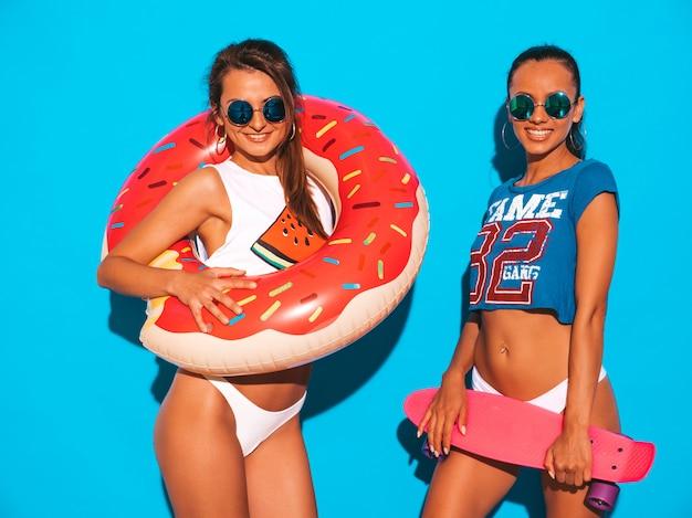 Dwie piękne uśmiechnięte seksowne kobiety w letnich majtkach i temacie. dziewczyny w okularach przeciwsłonecznych. pozytywne modele zabawy z kolorowymi deskorolkami grosza. z dmuchanym materacem lilo