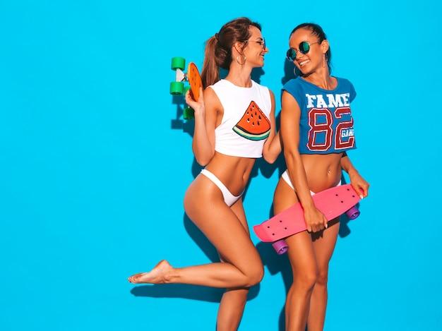 Dwie piękne uśmiechnięte seksowne kobiety w letnich majtkach i temacie. modne dziewczyny w okularach przeciwsłonecznych. pozytywne modele zabawy z kolorowymi deskorolkami grosza. odosobniony