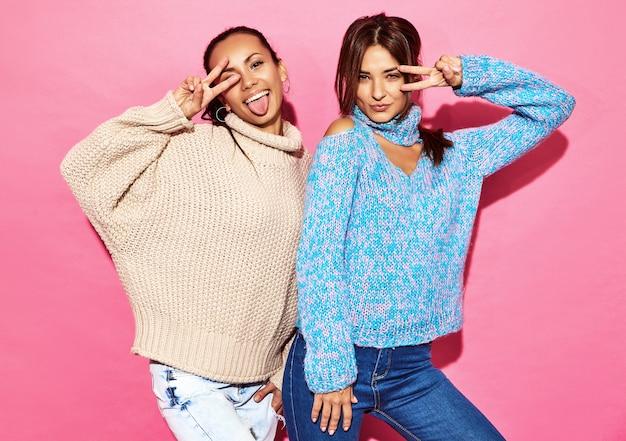 Dwie piękne uśmiechnięte wspaniałe kobiety. kobiety stojące w stylowych biało-niebieskich swetrach na różowej ścianie.