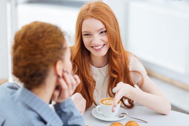 Dwie piękne wesołe młode kobiety siedzące razem w kawiarni in