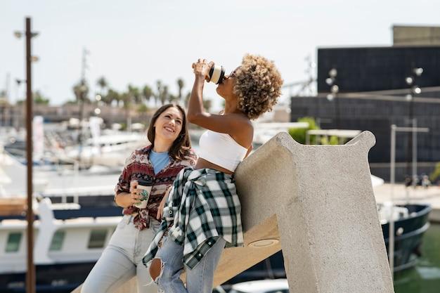 Dwie piękne wielorasowe kobiety, które spacerują po porcie z kawą, łódkami i jachtami w tle
