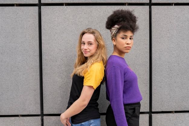 Dwie piękne wielorasowe kobiety na murze miejskim