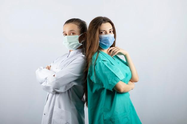 Dwie pielęgniarki w maskach medycznych patrzące na kamerę