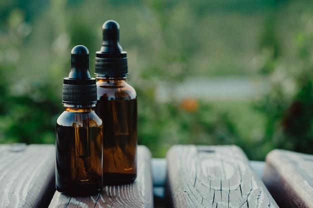 Dwie pipety i butelki olejku na tle przyrody. makieta butelki z zakraplaczem - dwie butelki.