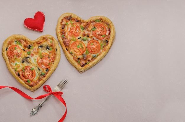Dwie pizze w formie serca na beżowym stole z czerwonym sercem z widelcem z czerwoną wstążką. zamów pizzę na romantyczną kolację w walentynki. miłość.-