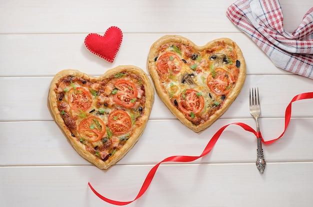 Dwie pizze w formie serca na białym drewnianym stole z widelcem z czerwoną wstążką z czerwonym sercem. romantyczna kolacja na walentynki, kochanie.
