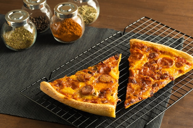 Dwie pizze z polewą pepperoni na stojaku chłodzącym na czarnej podkładce z tkaniny oraz grupa ziół i przypraw w słoikach na konwerterze