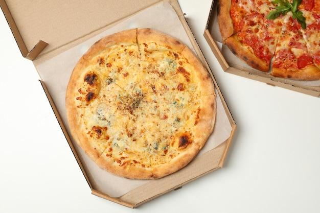 Dwie pizzy w pudełkach kartonowych na białym tle