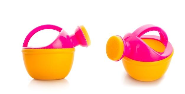 Dwie plastikowe konewki z zabawkami na białym tle