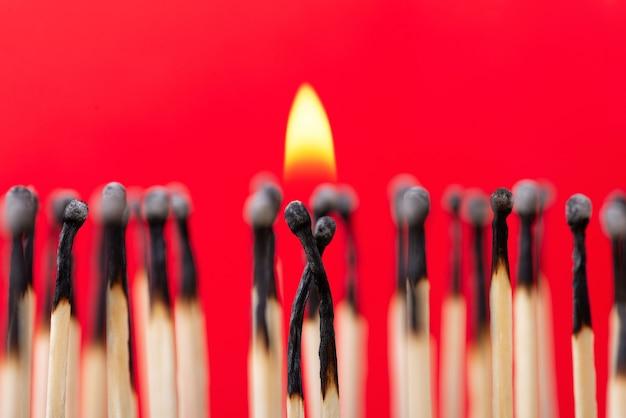 Dwie płonące zapałki stojące blisko siebie z małym ogniem symbolizującym miłość, pasję, związek