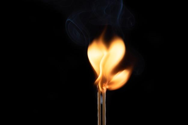 Dwie płonące zapałki z dymem i ogniem w formie serca