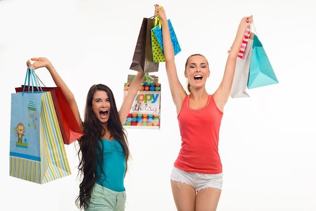 Dwie podekscytowane dziewczyny z torbami na zakupy.