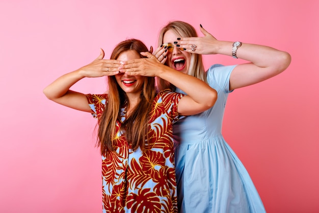 Dwie podekscytowane kobiety uśmiechające się i zamykające oczy dłońmi, ubrane w kolorowe sukienki