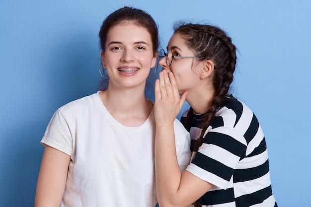 Dwie podekscytowane młode dziewczyny ubrane w letnie ubrania plotkują na białym tle, pani w okularach szepcząca coś do ucha, dziewczyny wyrażające radość.