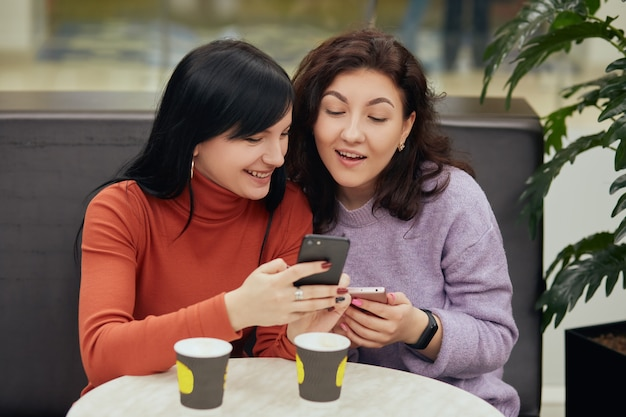 Dwie podekscytowane młode kobiety korzystające z telefonów komórkowych, siedzące przy stole w kawiarni i pijące gorące napoje, brunetki spoglądające na ekran smartfona i czytające coś ciekawego.