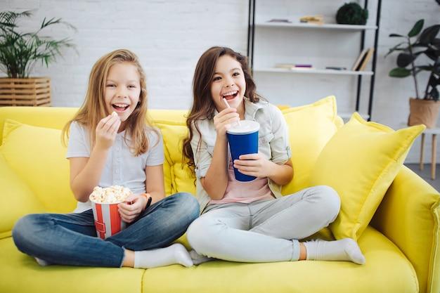 Dwie podekscytowane nastolatki siedzą na kanapie i patrzą do przodu. trzymają busket z popcornem i filiżanką coli. dziewczyna trzymaj nogi skrzyżowane. uśmiechają się i radują.
