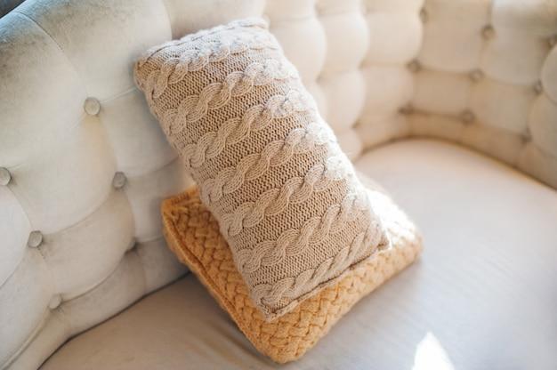 Dwie poduszki leżące na kanapie z bliska