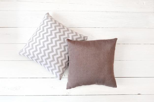 Dwie poduszki na białej drewnianej powierzchni