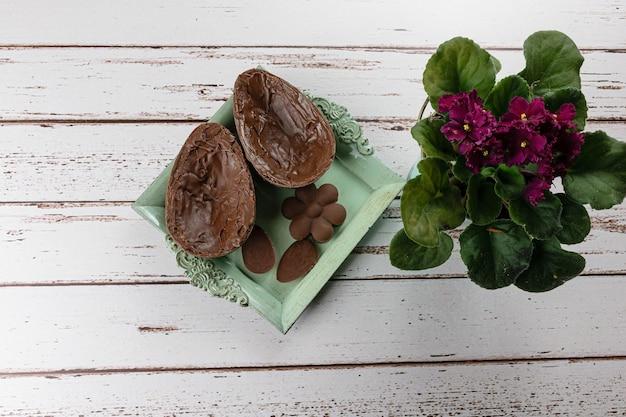 Dwie połówki czekoladowego jajka wielkanocnego na małej starej tacy. obok mini czekoladek i kwiatów.