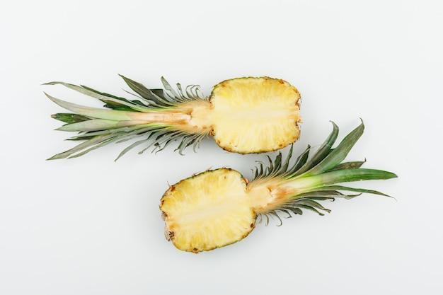 Dwie połówki dojrzałego ananasa na bielu. widok z góry.