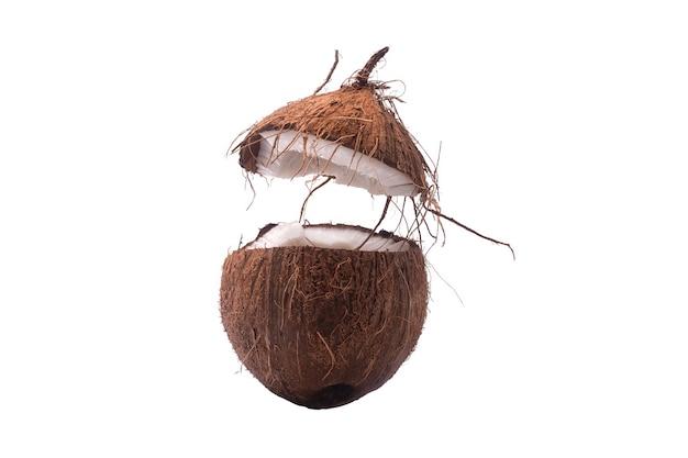 Dwie połówki sekcji kokosa na białym tle, jedna złamana na pół