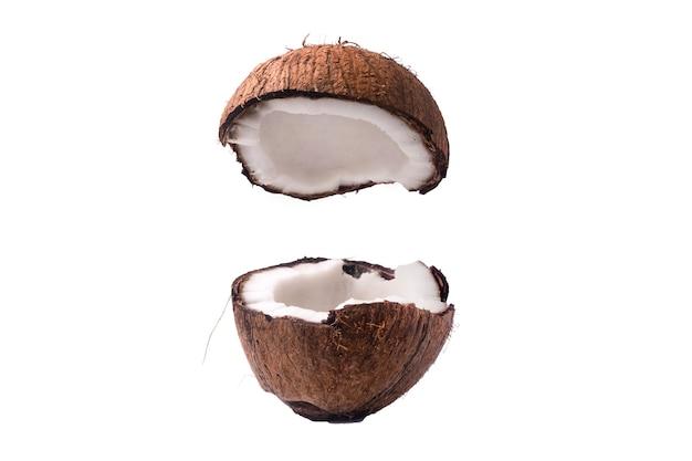 Dwie połówki sekcji orzecha kokosowego na białym tle, jedna złamana w dwóch brązowych włóknistych skorupkach z mięsem mlecznym