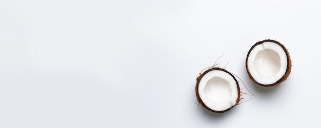 Dwie połówki surowego kokosa na szarym tle. koncepcja zdrowej żywności