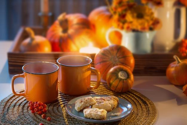 Dwie pomarańczowe filiżanki herbaty i jesienny wystrój z dyniami, kwiatami i płonącymi świecami na stole