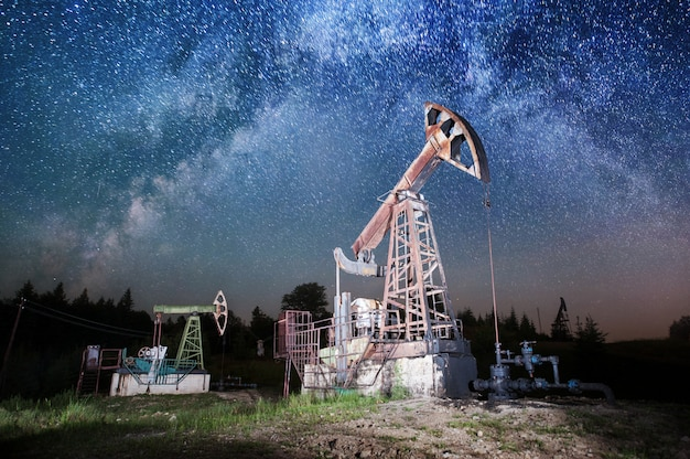 Dwie pompy olejowe pracują na polu naftowym, urządzenia przemysłu naftowego.