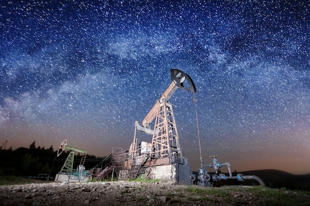 Dwie pompy olejowe pracujące w nocy na polu naftowym pod drogą mleczną. sprzęt przemysłu naftowego