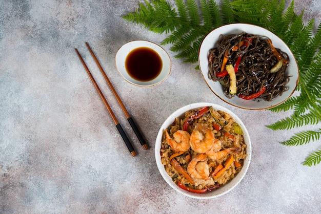 Dwie popularne azjatyckie potrawy stoją na betonowej ścianie. chahan smażony ryż z jajkiem i warzywami oraz makaron gryczany z warzywami w sosie sojowym. poziome zdjęcie. widok z góry.