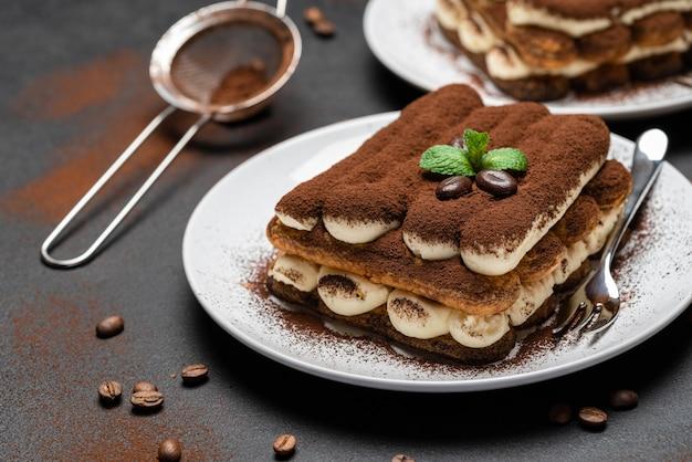 Dwie porcje deseru tiramisu classic na talerzu ceramicznym na betonowym tle lub stole