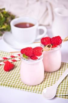 Dwie porcje naturalnego jogurtu domowego w szklanych słoikach ze świeżymi malinami
