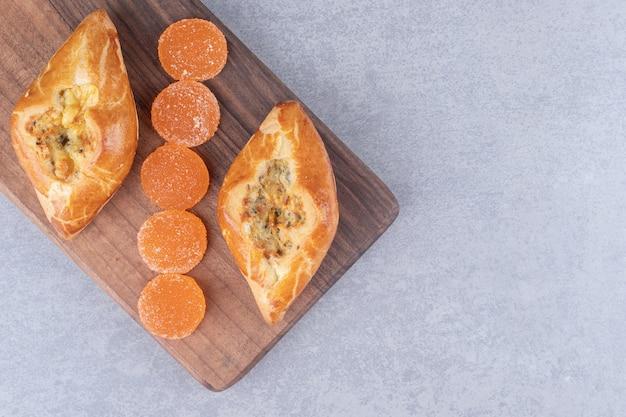 Dwie porcje pide i marmolad na drewnianej desce na marmurowym stole.