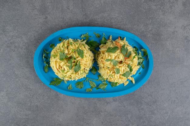 Dwie porcje pysznego ryżu na niebieskim talerzu. zdjęcie wysokiej jakości