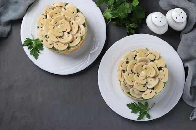 Dwie porcje sałatki francuskiej z kurczakiem, marynowanymi grzybami, ziemniakami i marchewką na talerzach. widok z góry.