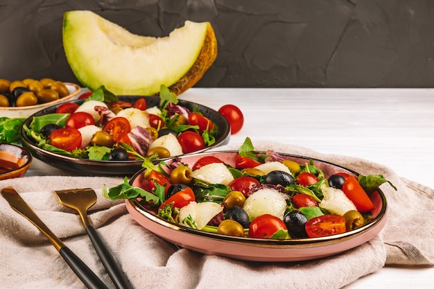 Dwie porcje sałatki z melonem, pomidorami i oliwkami na stole